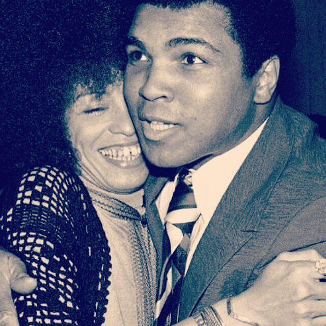 Muhammad Ali and Angela Davis sharing a good-spirited embrace.