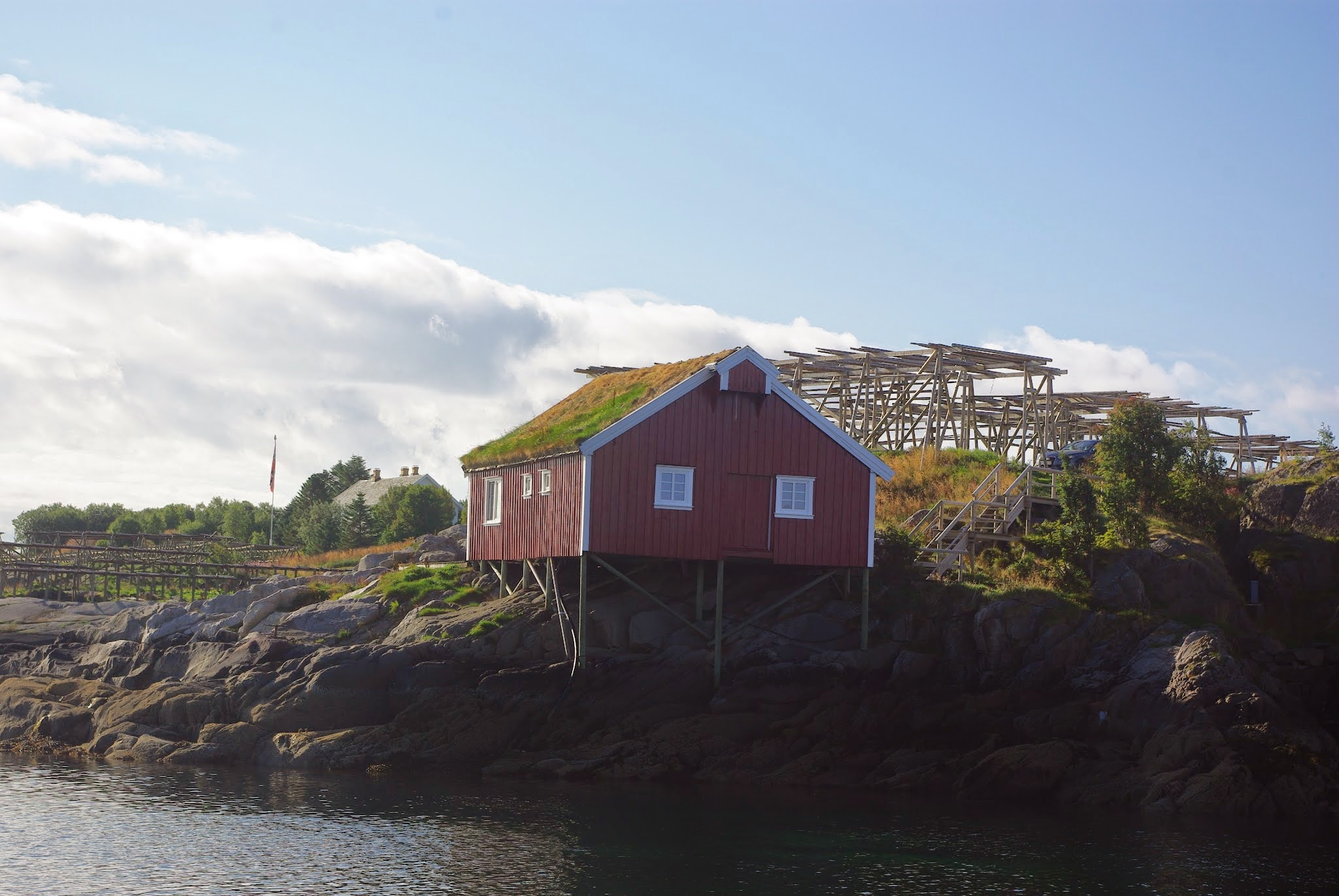 A traditional sod roof on a fjord-side building near Reine. You can also see some cod-drying racks behind it, a common sight in the area.
