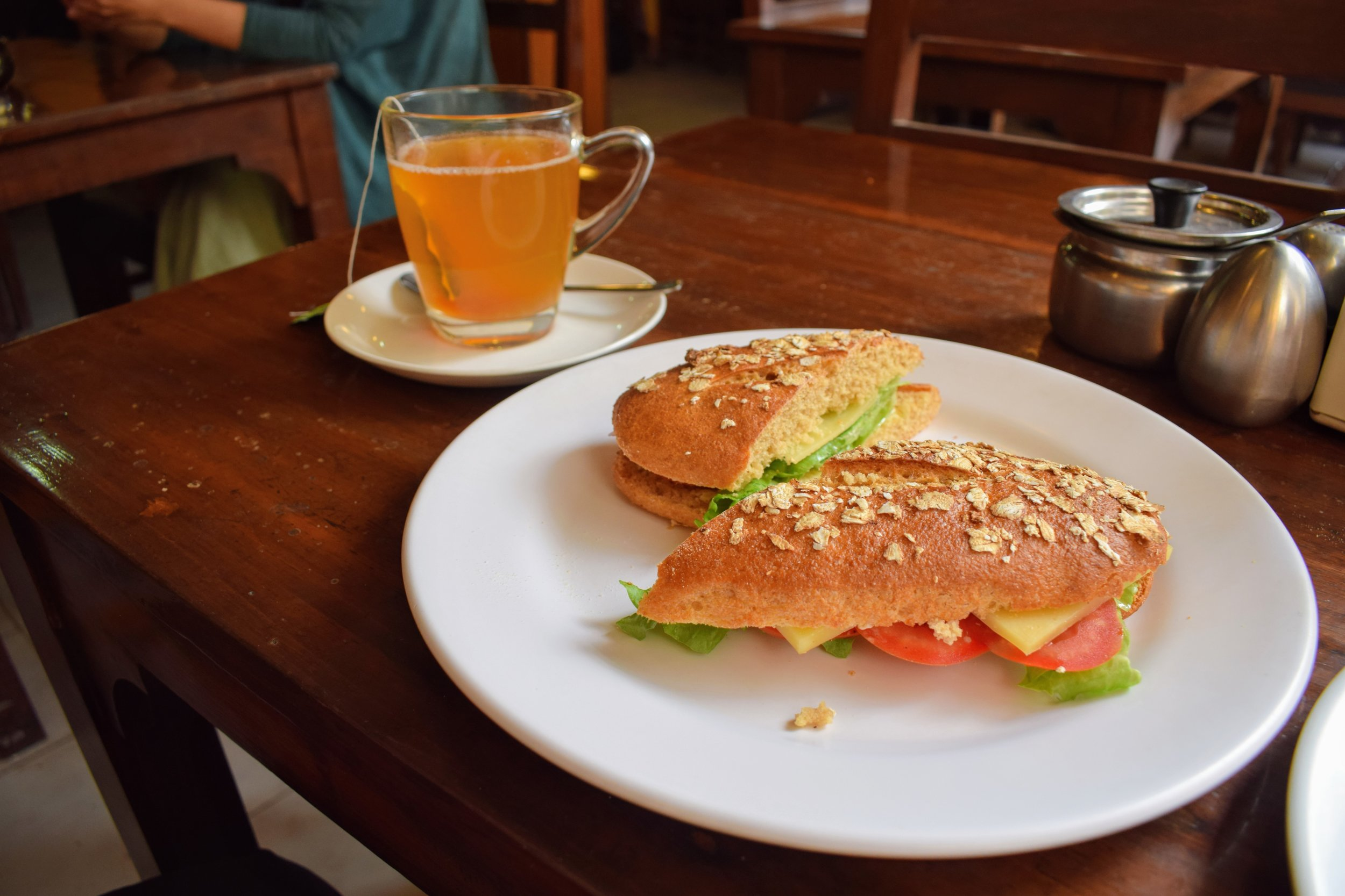 Ginger lemon honey tea and a yak cheese sandwich on fresh bread at Pumpernickel Bakery in Thamel.