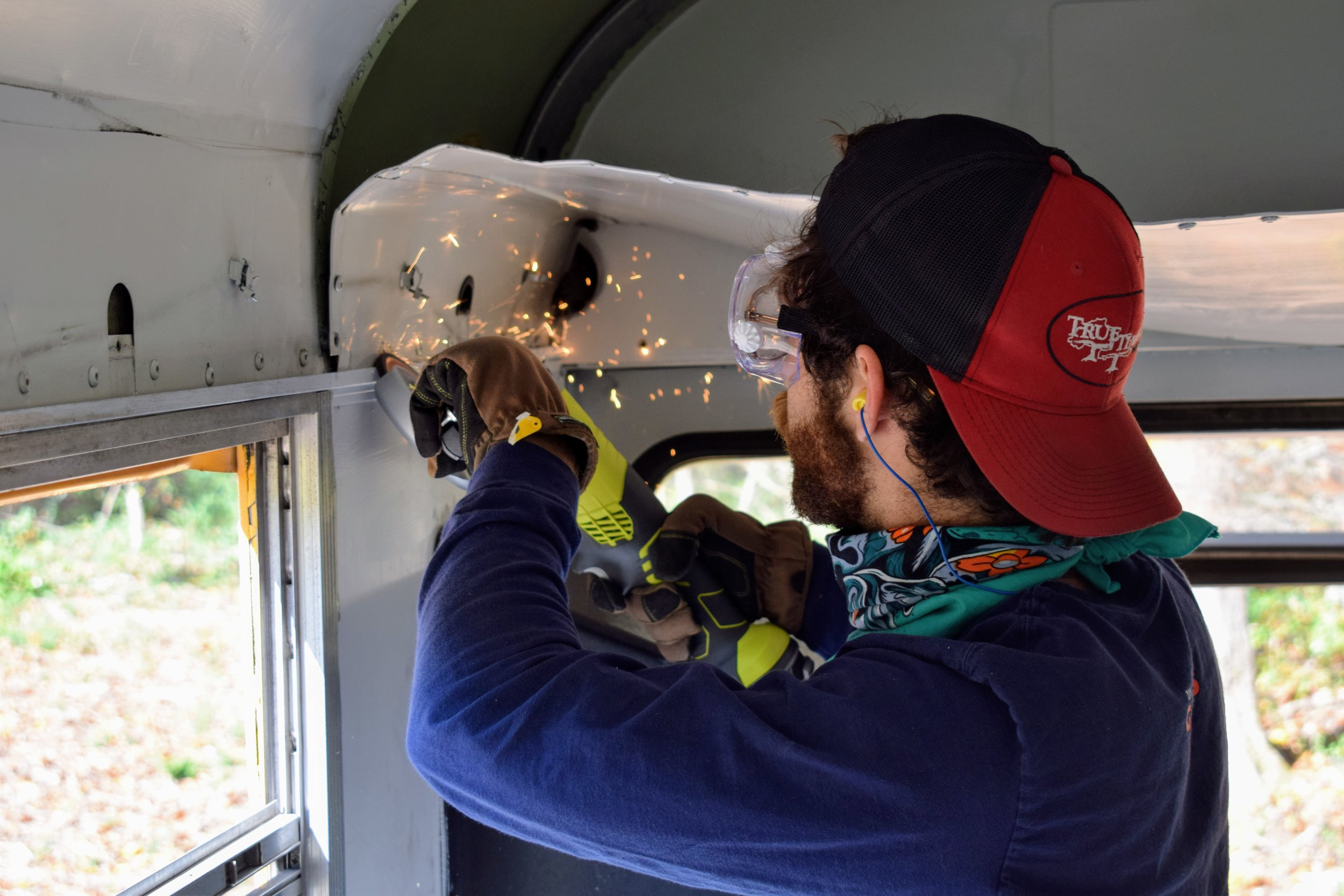Emmett grinding off stripped screws on the ceiling panels of our bus.