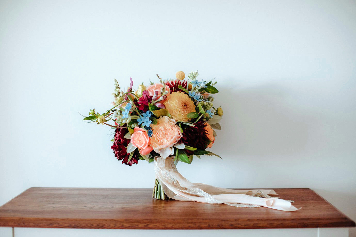 Bright mix of roses, dahlias, tweedia, craspedia and snapdragons. Captured by  Chasewild