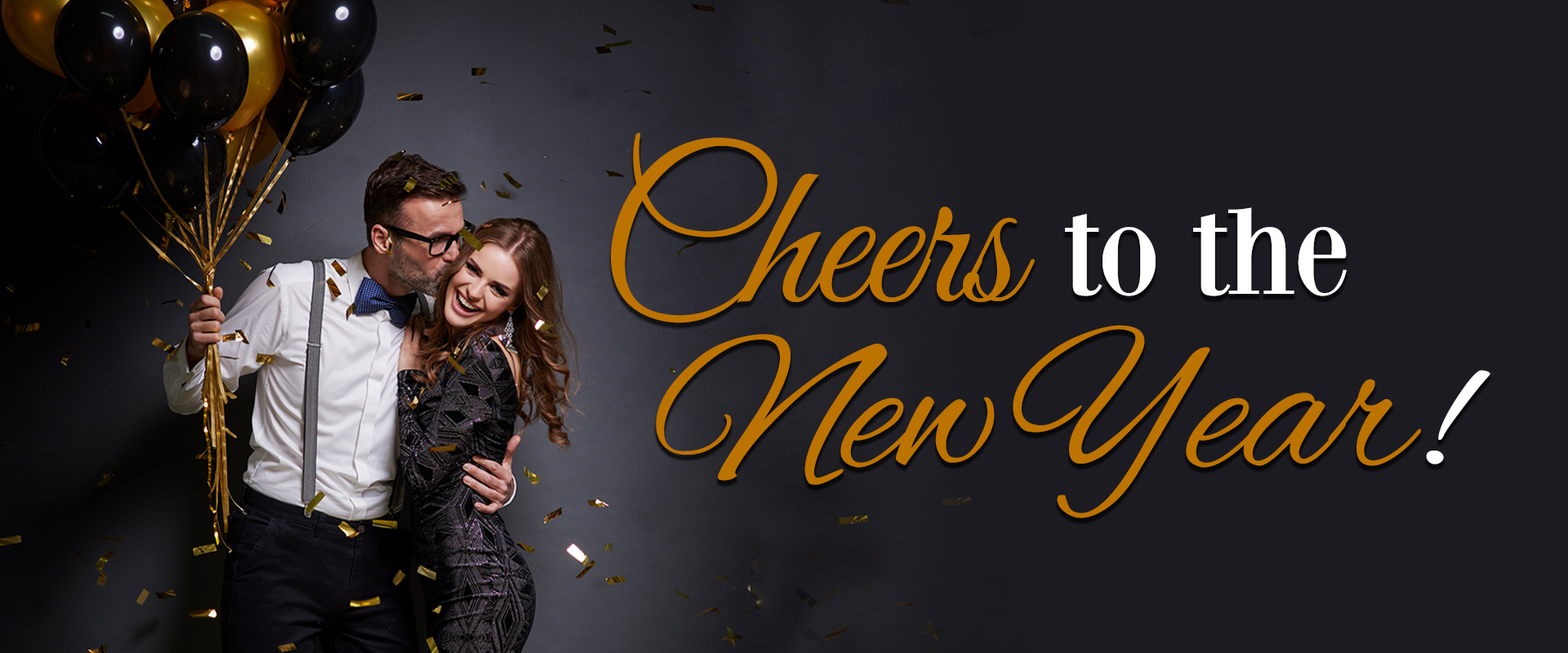 Couple celebrating the new year with black and gold balloons and confetti  with the text Cheers to the New Year over layed