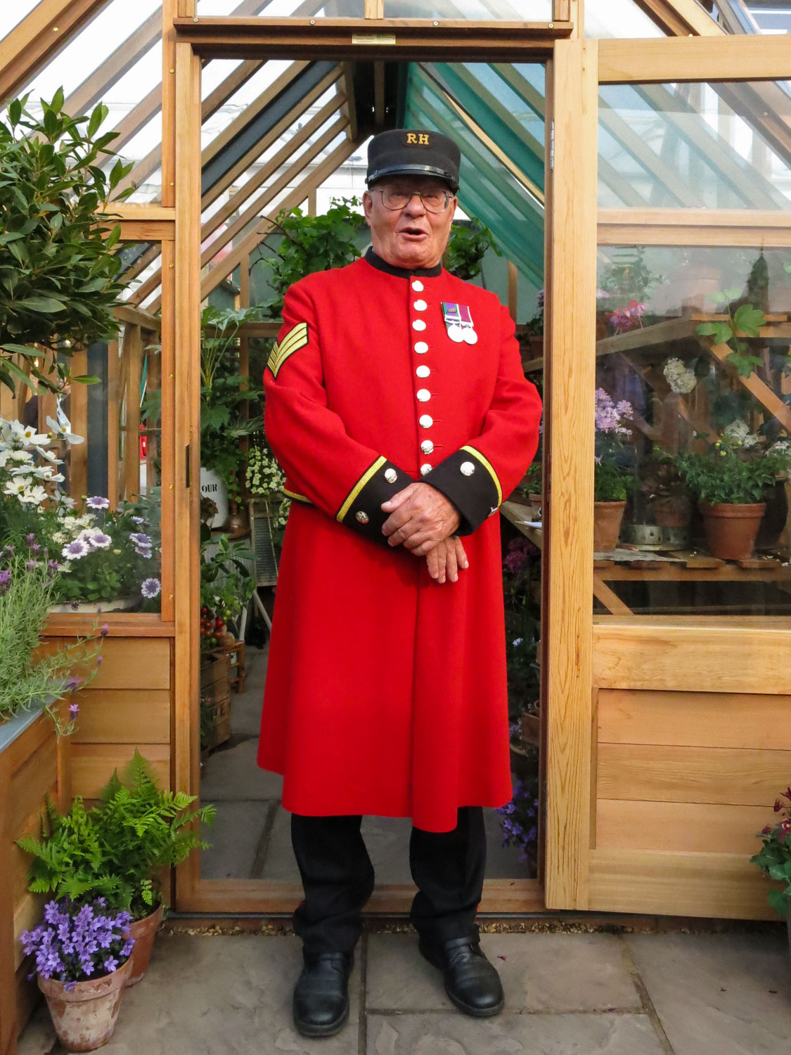 Chelsea Pensioner in front of the Gabriel Ash Hyde Hall Greenhouse.  RHS Chelsea Flower Sho