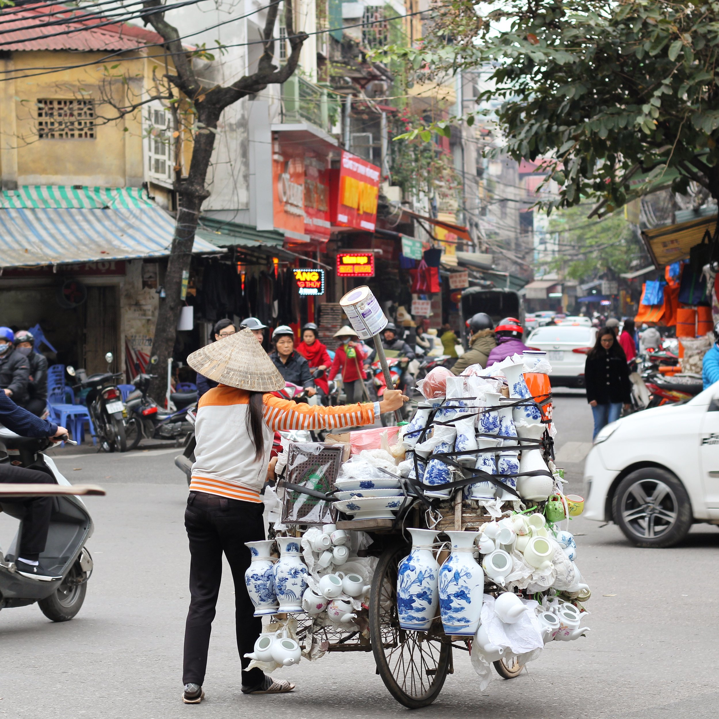 A woman bravely shuttling her pottery cart into the bustling street traffic.