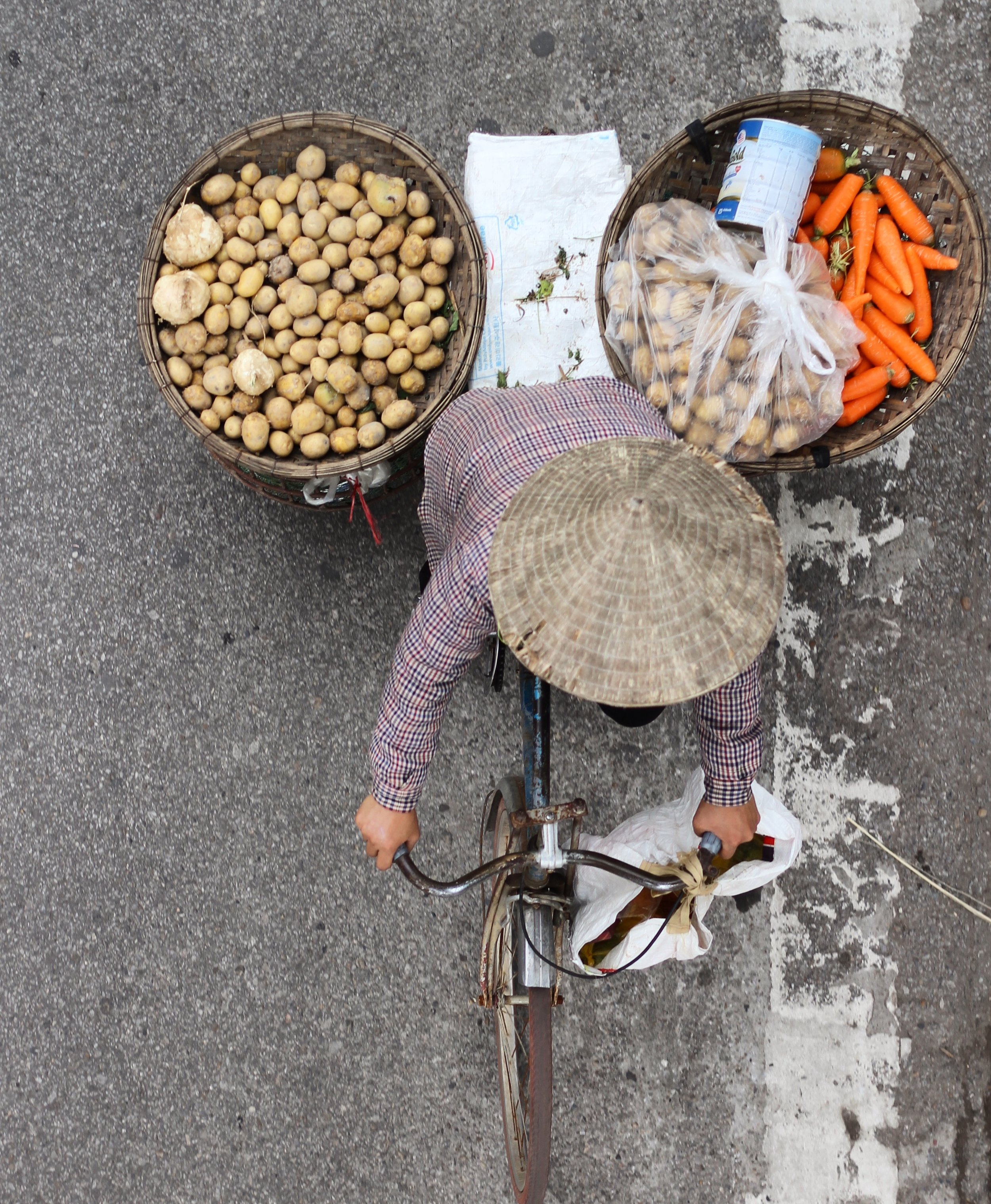 A woman biking through Hanoi with her vegetables.