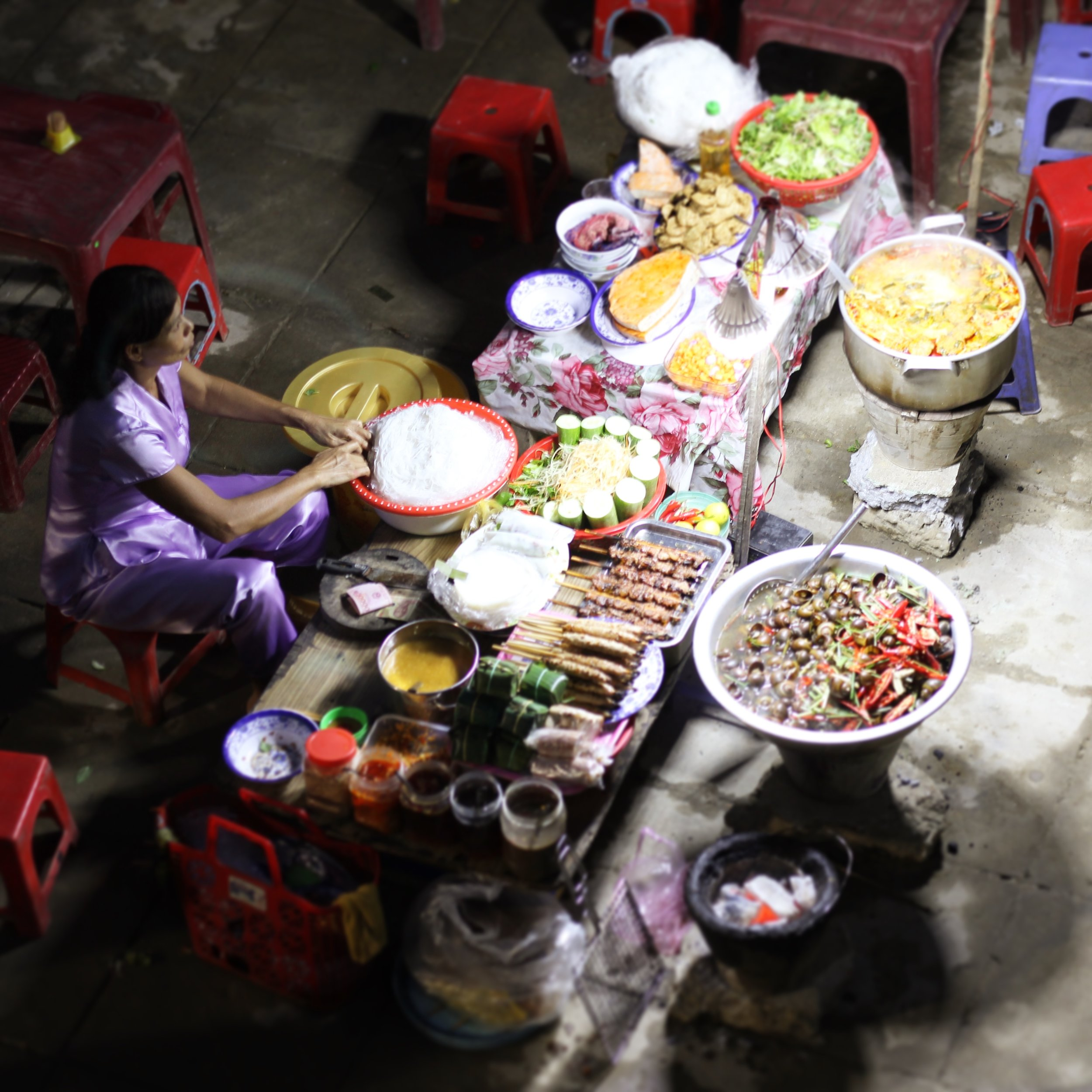 A woman cooking at her colorful street stand at night in Hue.