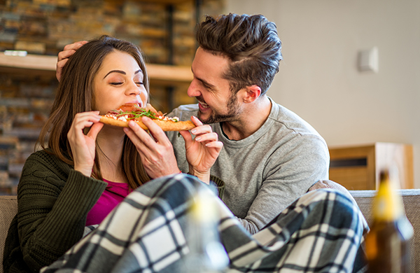 couple-sitting-on-sofa-eating-takeout-gourmet-pizza_jpg-600x390.jpg