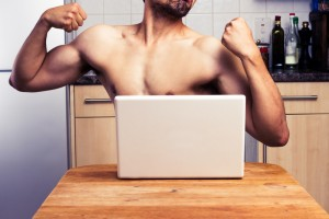 A man flexing in front of computer