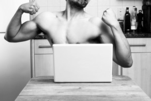 A guy flexing his arms in front of a computer