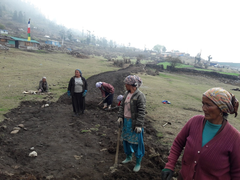 Members of Melamchi community digging out the new road in the village