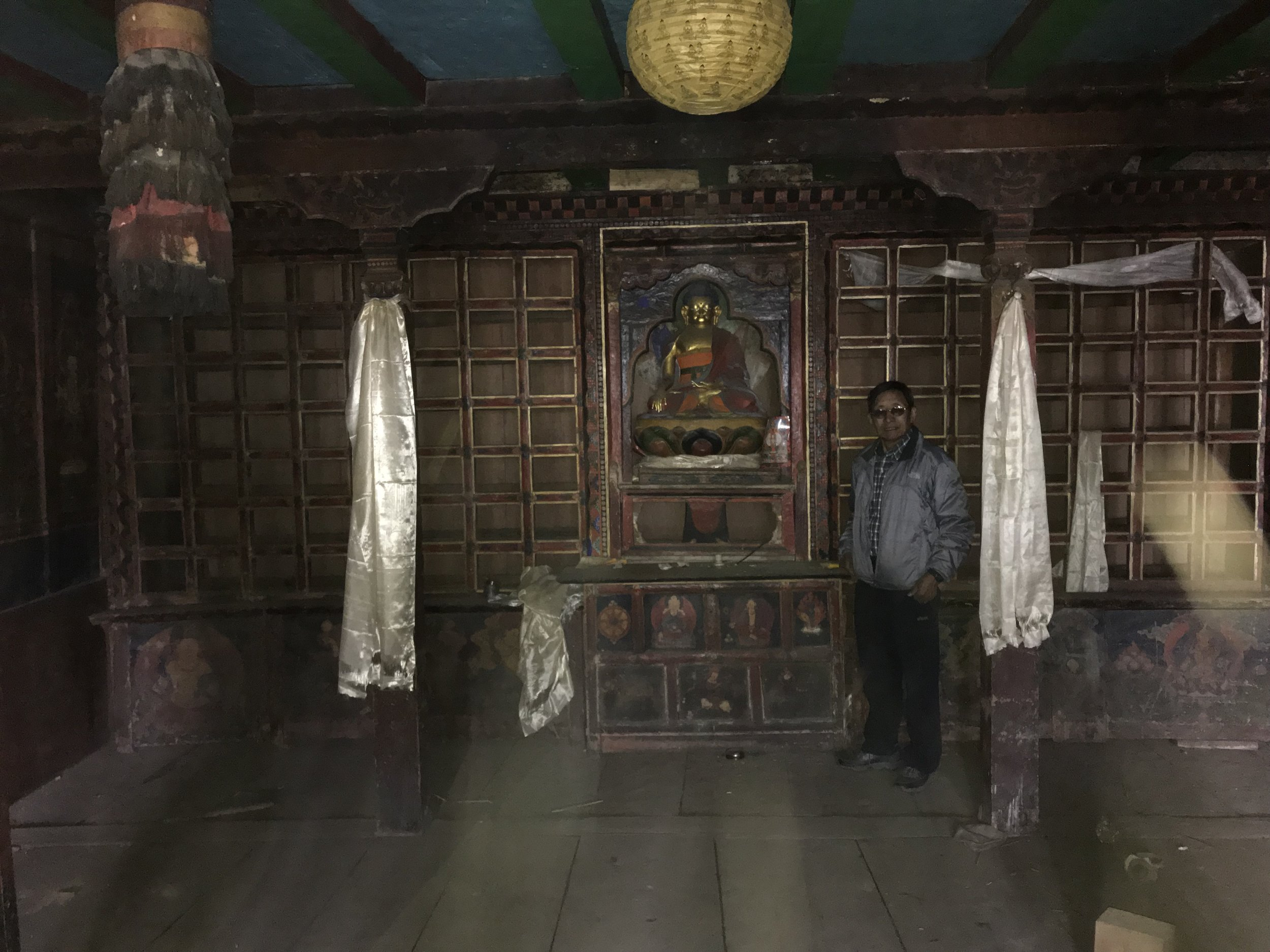 Pertemba standing in from of the statue of Buddha with the empty prayer scroll racks. All prayer scrolls were placed in safe storage.