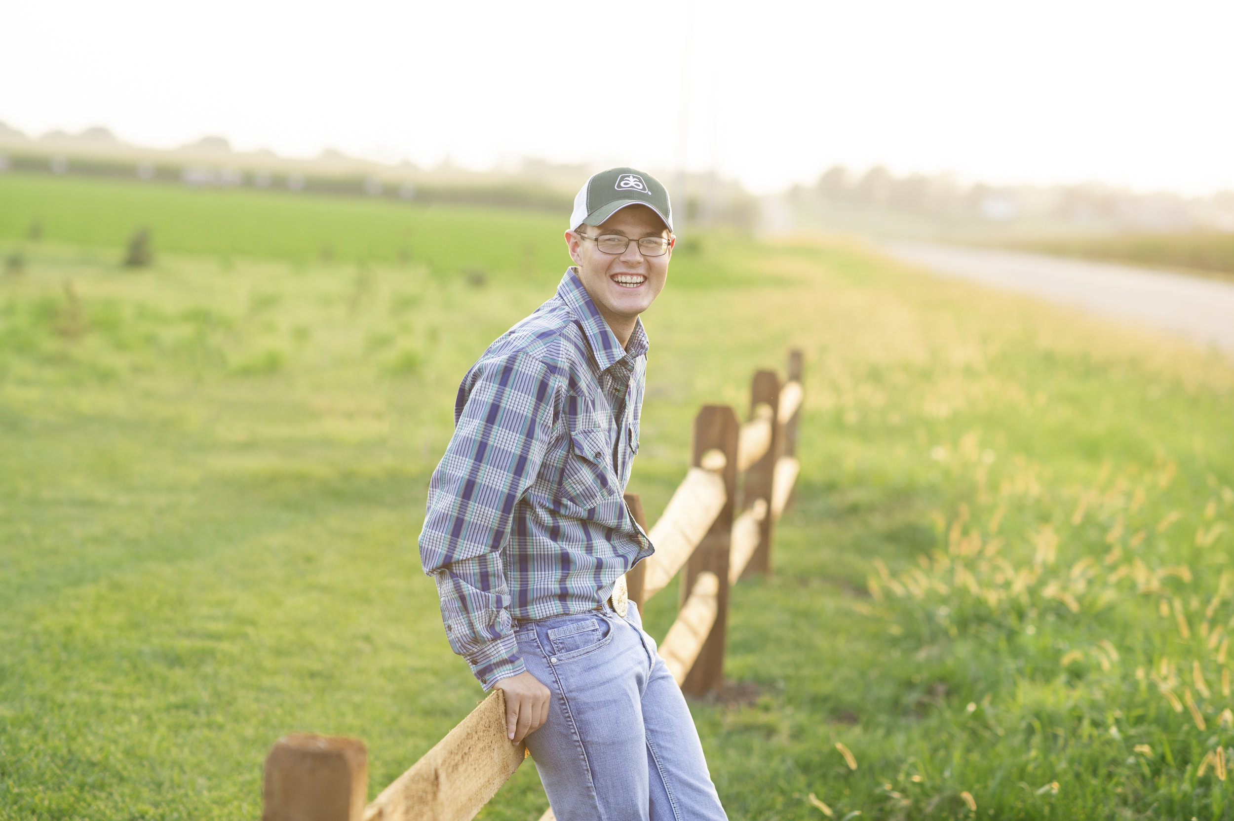 dirt-road-photography-kelsey-nerudwilber-nebraska-southeast-photographer-senior-farm-grass-sunshine-sunflare-sunset-guy-boy-senior-high-school-wilber-clatonia-southeast-nebraska-photgrapher-photography-green-grass-wood-fence-glasses-plaid-shirt-jeans-boots-belt-buckle-seed-company-baseball-cap