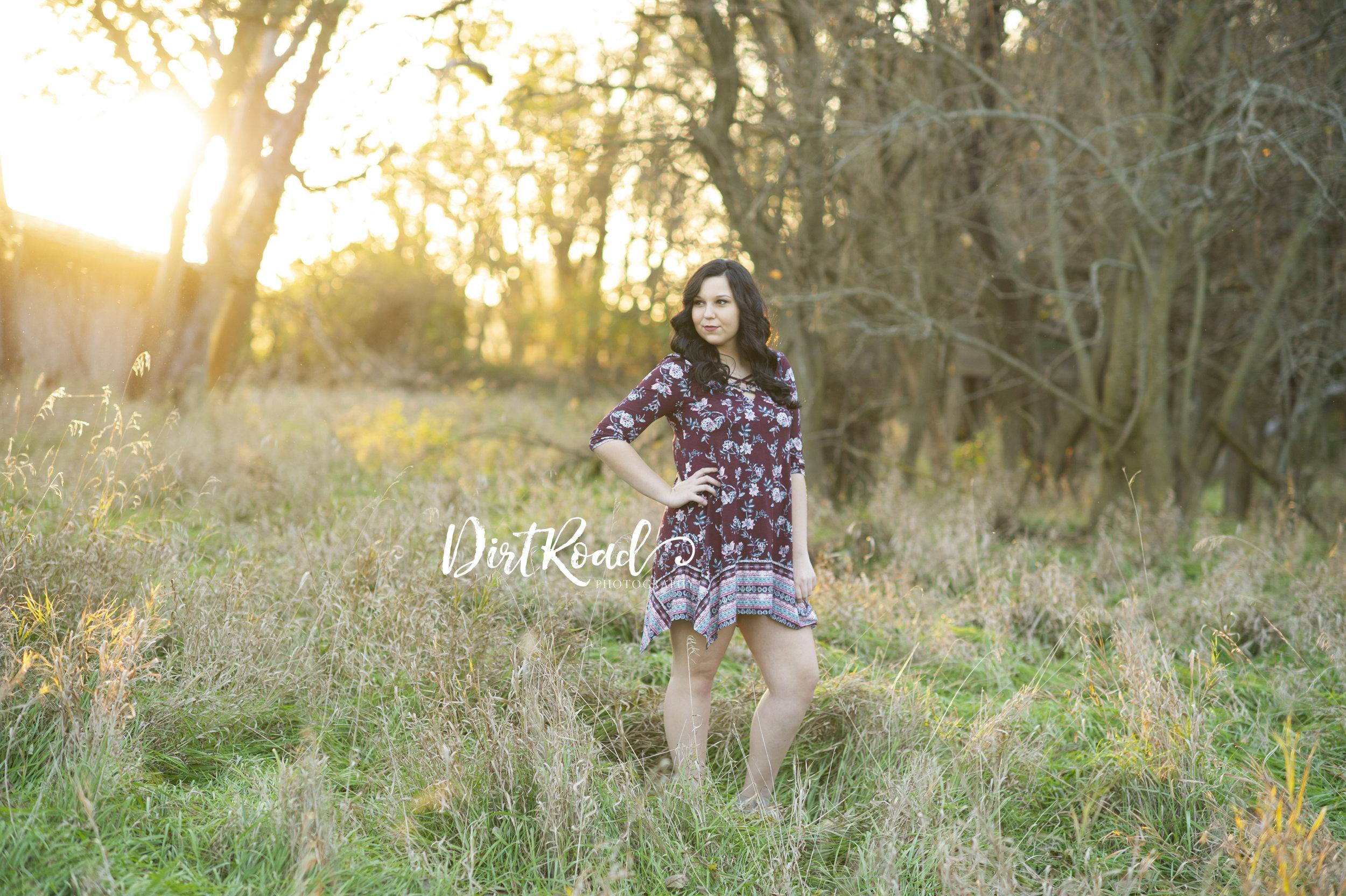 dirt-road-photography-kelsey-homolka-nerud-wilber-nebraska-southeast-photographer-senior-farm-grass-sunshine-sunflare-sunset-girl-senior-high-school-fairbury-high-southeast-nebraska-photgrapher-photography-green-grass-wood-fence-glasses-brown-hair-maroon-dress-destiny-brown