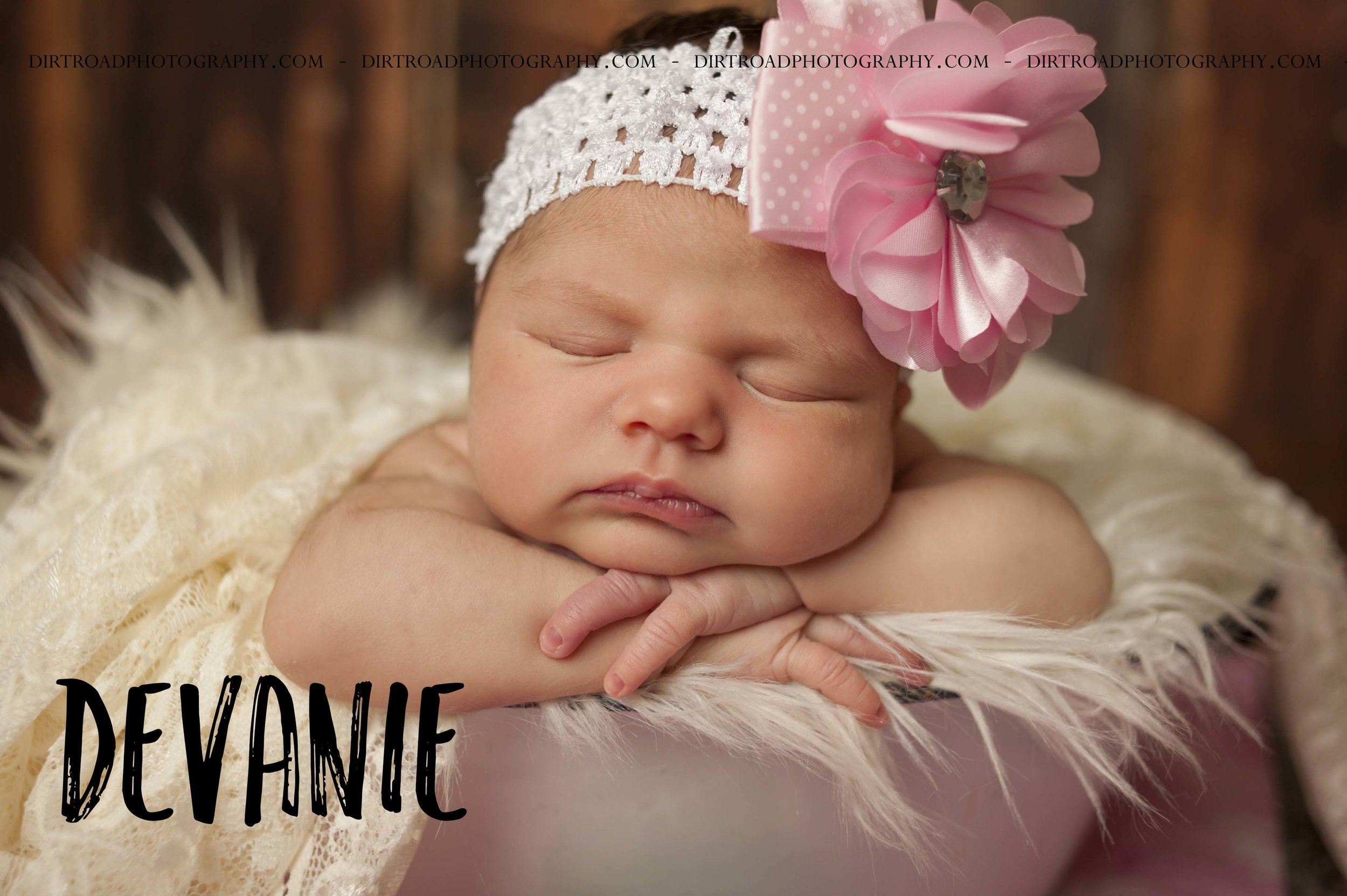 devanie newborn photos of ten day old baby with big pink bow and dark longer brown hair sitting in porcelain bowl with white fluffy layer and lace blanket laying on it photos taken near wilber nebraska at studio with dirt road photography by kelsey nerud the photographer