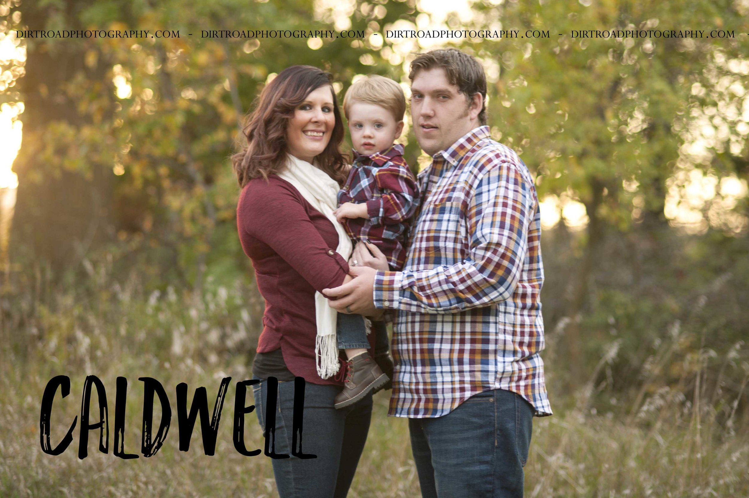 nebraska photographer kelsey homolka nerud takes family portrait session photos of family from lincoln nebraska photo is of a family of three with maroon and plaid colored outfits at sunset on a farm with tall grass and a one year old baby boy