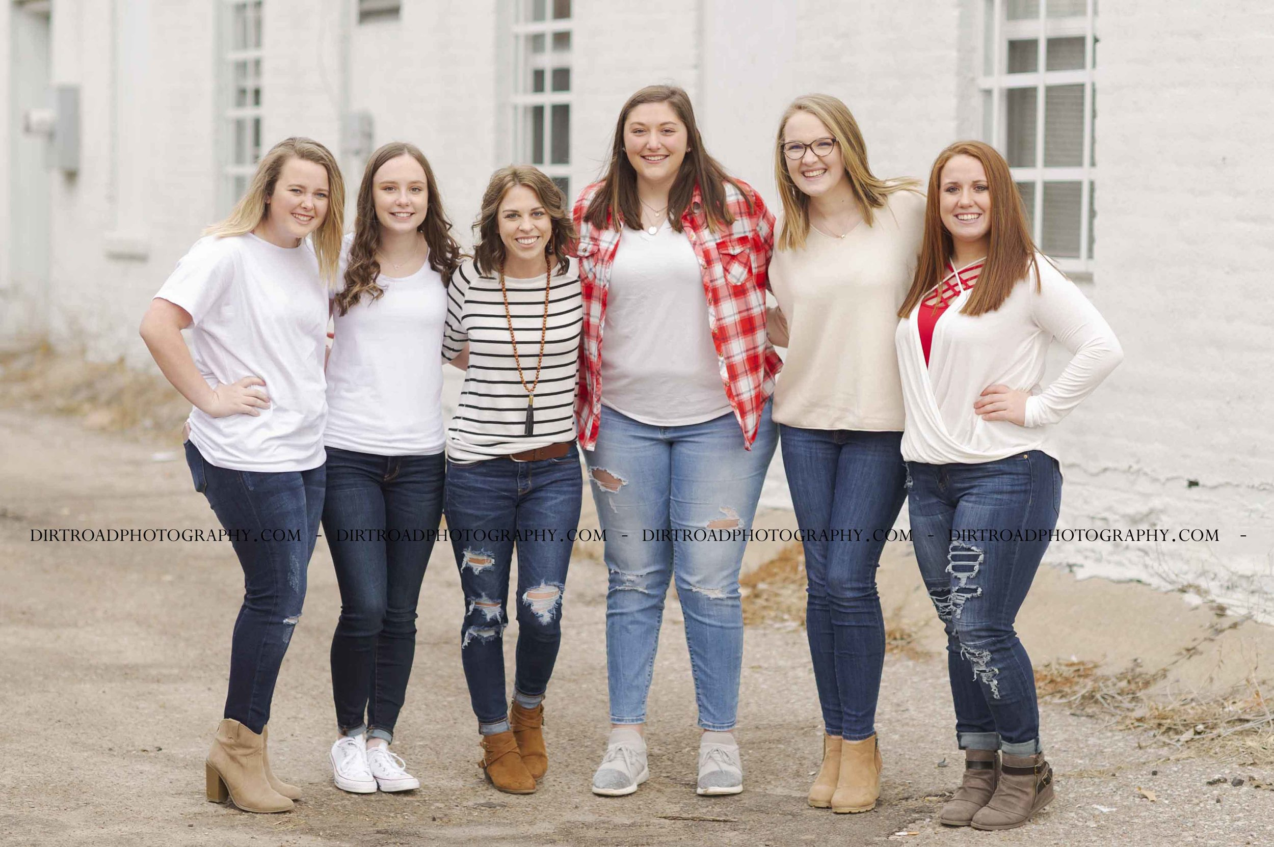 picture of high school senior girls from high schools in nebraska including wilber-clatonia high school, milford high school, friend high school, tri-county high school and norris high school. girls are in blue jeans with cream and white sweaters and winter boots, laughing with each other in an urban alley with white brick wall behind them. girls talking and taking pictures for high school photography dirt road photography by kelsey homolka nerud photographer.
