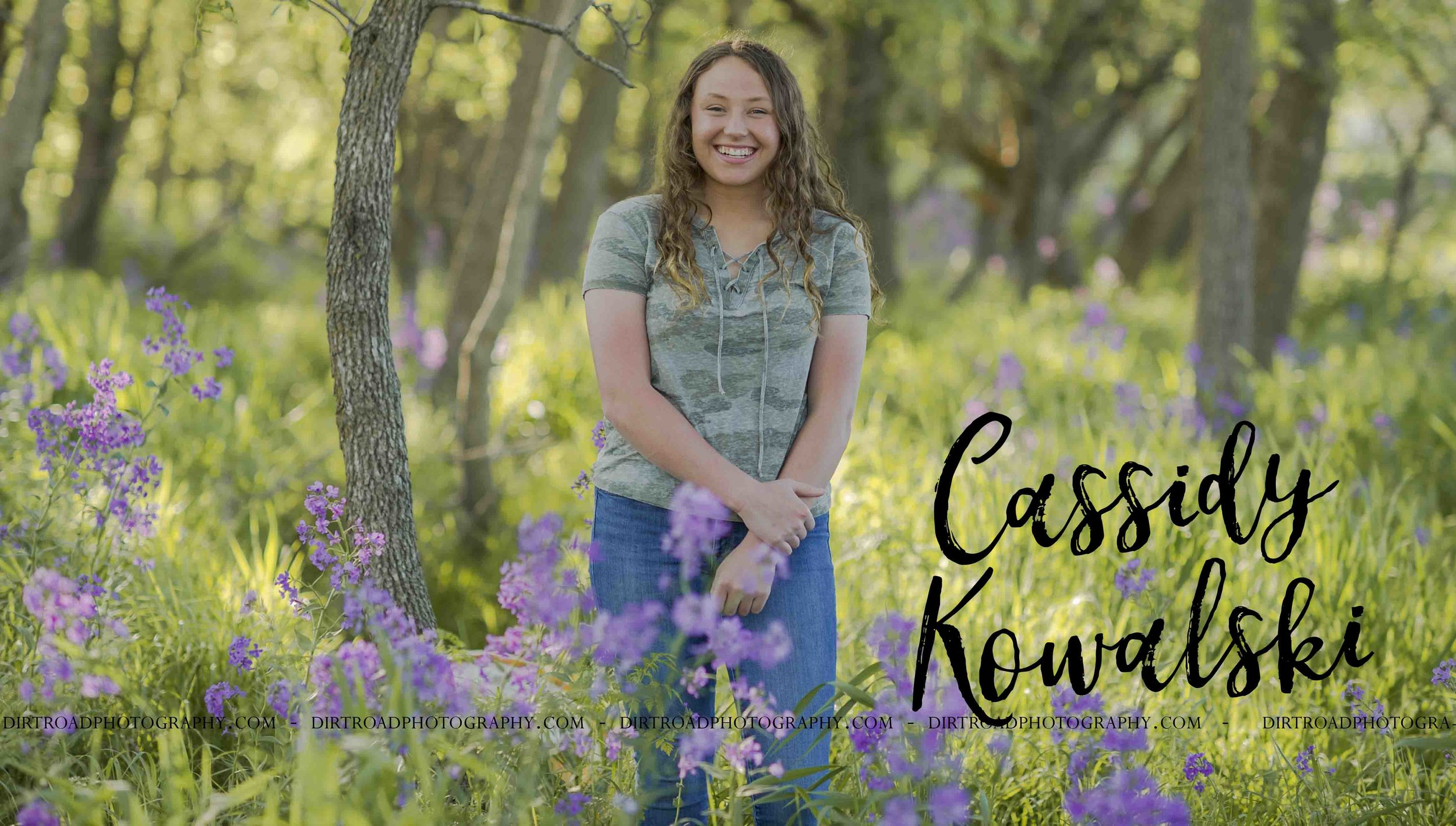 images of high school girl senior photos named cassidy kowalski of wilber nebraska who went to tri-county high school in nebraska and is part of the class of 2020. photos were taken near swanton nebraska in saline county. photo includes purple spring flowers at sunset with girl in camo lace up t-shirt and jeans standing in tall natural grass with trees surrounding her. teen has curly long brown hair. photos taken at sunset near water and farm pond. photographer is kelsey homolka nerud of wilber nebraska who specializes in high school senior photography and senior pictures.