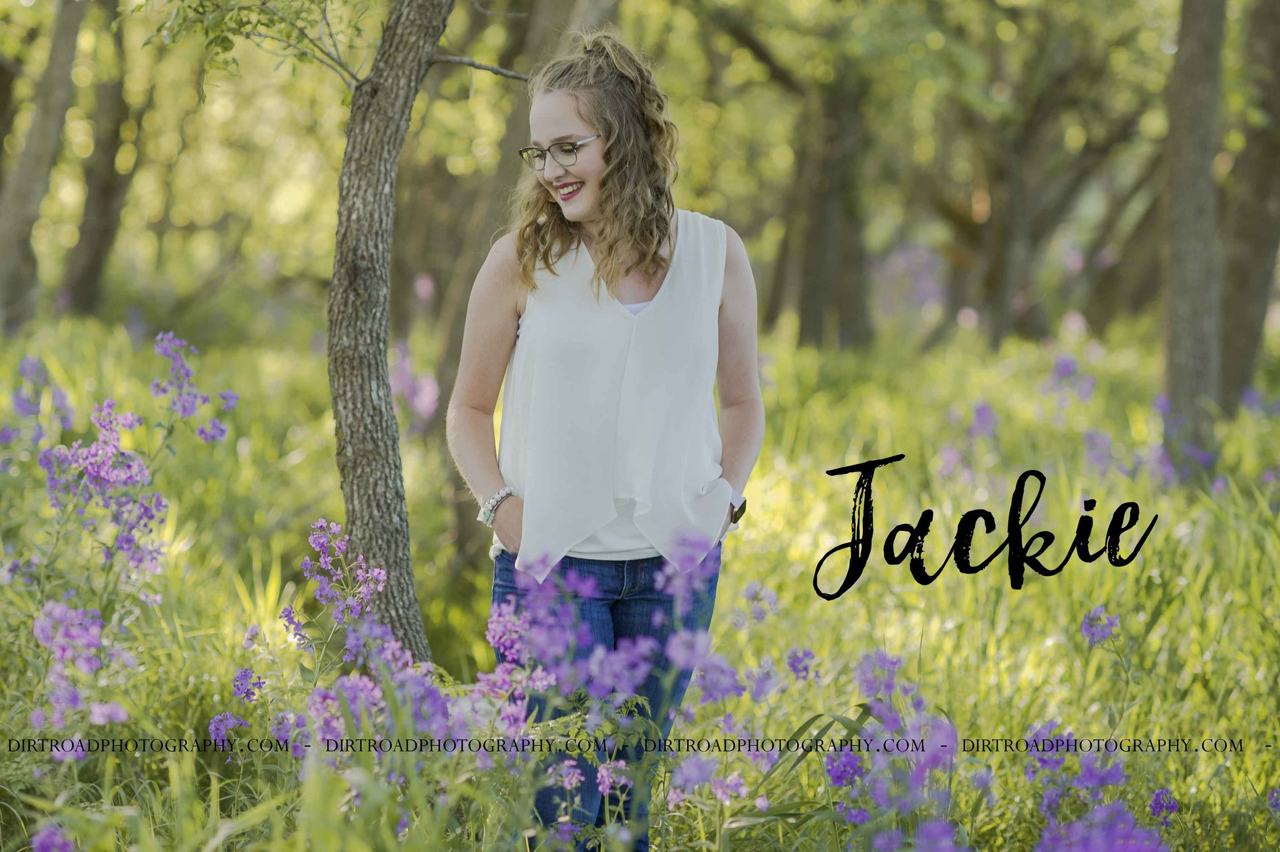 images of high school girl senior photos named jackie kalkwarf of wilber nebraska who went to wilber-clatonia high school in nebraska and is part of the class of 2020. photos were taken near swanton nebraska in saline county. photo includes purple spring flowers at sunset with girl in white flowy shirt and jeans standing in tall natural grass with trees surrounding her. teen has curly long brown hair. photos taken at sunset near water and farm pond. photographer is kelsey homolka nerud of wilber nebraska who specializes in high school senior photography and senior pictures.