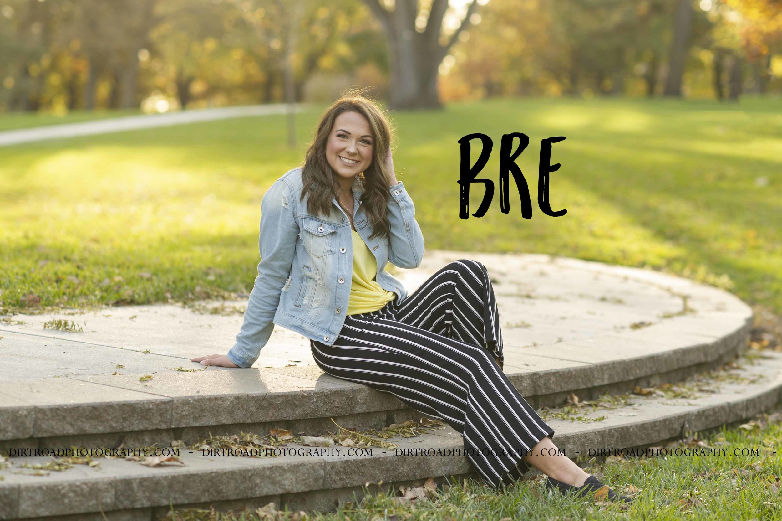 images of high school girl senior photos named bre zoubek of wilber nebraska who went to wilber-clatonia high school in nebraska and is part of the class of 2019. photos were taken near crete nebraska in saline county at doane university formerly doane college of crete. photo includes tall glass buildings, brick and cement bridges, fall leaves, sunsets, pond with swans, and dirt roads. girl is dressed in striped black and white pants, steven madden shoes, yellow tank top with denim jacket with long brown hair and styled make-up. dirt road surrounded by trees and dust at sunset. tall grass with a sunset behind as well. photographer is kelsey homolka nerud of wilber nebraska who specializes in high school senior photography and senior pictures.