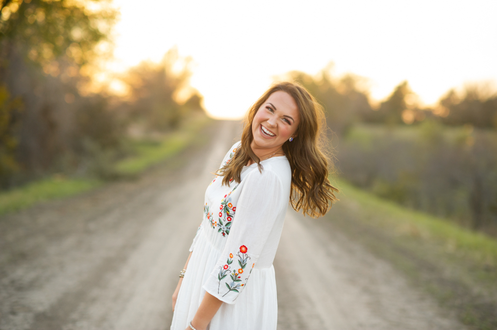 high school senior girl portrait photographer in dorchester nebraska photos of breanna zoubek of wilber nebraska with flowers, streams, sunset, tall grass, dirt roads, sun dresses, fall leaves, and trees