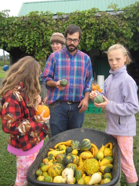 Children picking gourds from a wheelbarrow