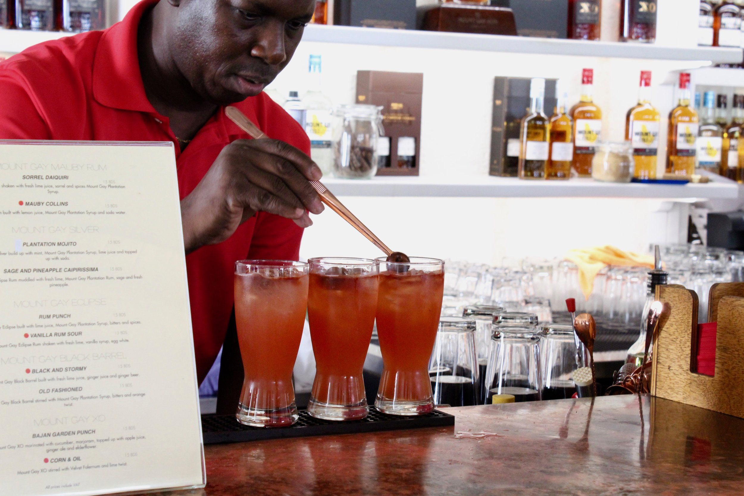 Bartender finishing off rum punches with rum soaked cherries, Mount Gay Distillery