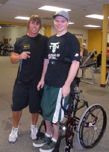Joey (in a standing wheelchair) with his trainer, David.