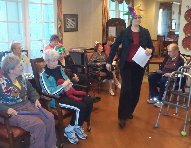 Rabbi Avivah shares the festive Jewish holiday of Purim with facility residents. At right, she leads a mock Passover Seder.