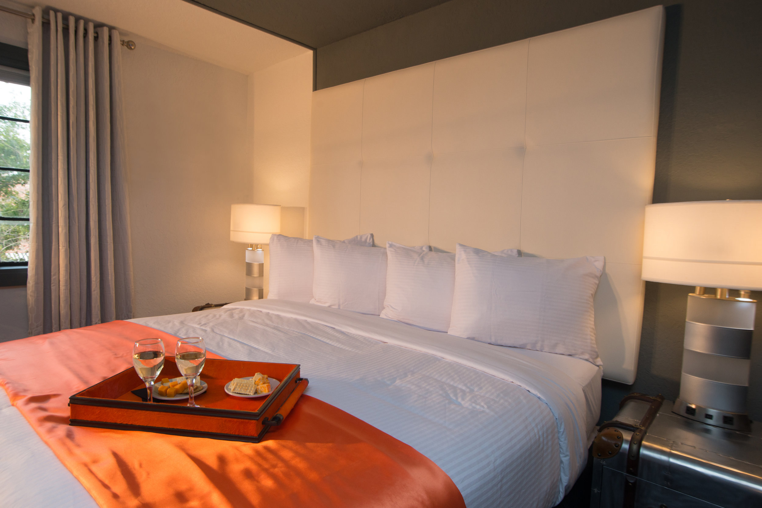 Interior of Deluxe King room with a tray of wine and food on top of bed.