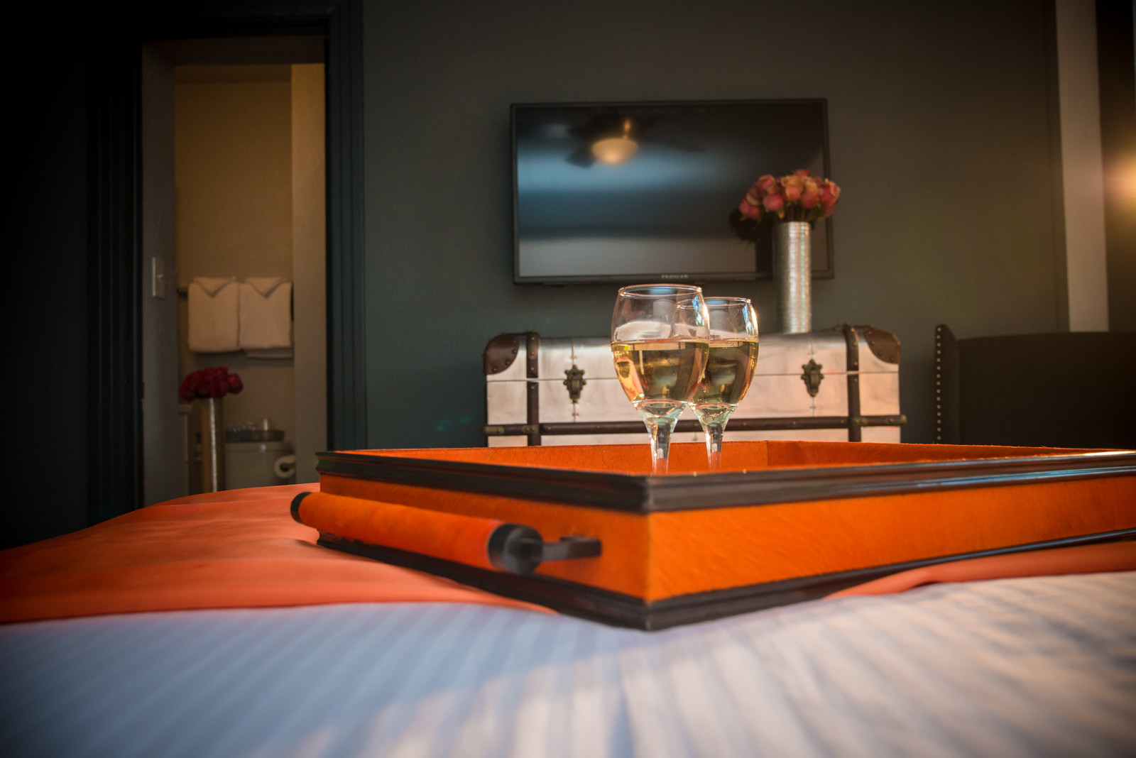 2 glasses of wine on a tray on top of bed in Queen Room.