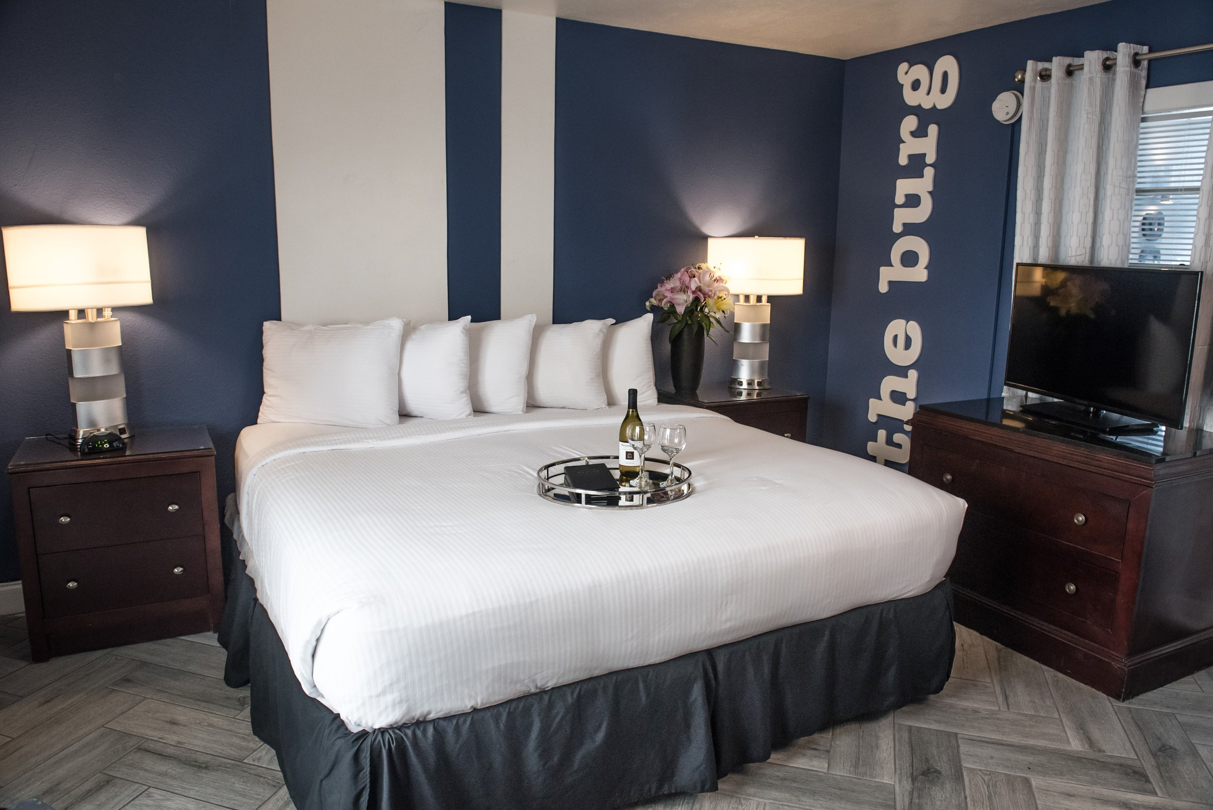 Interior of Studio Suite with a tray of wine and food on top of bed and flat screen TV