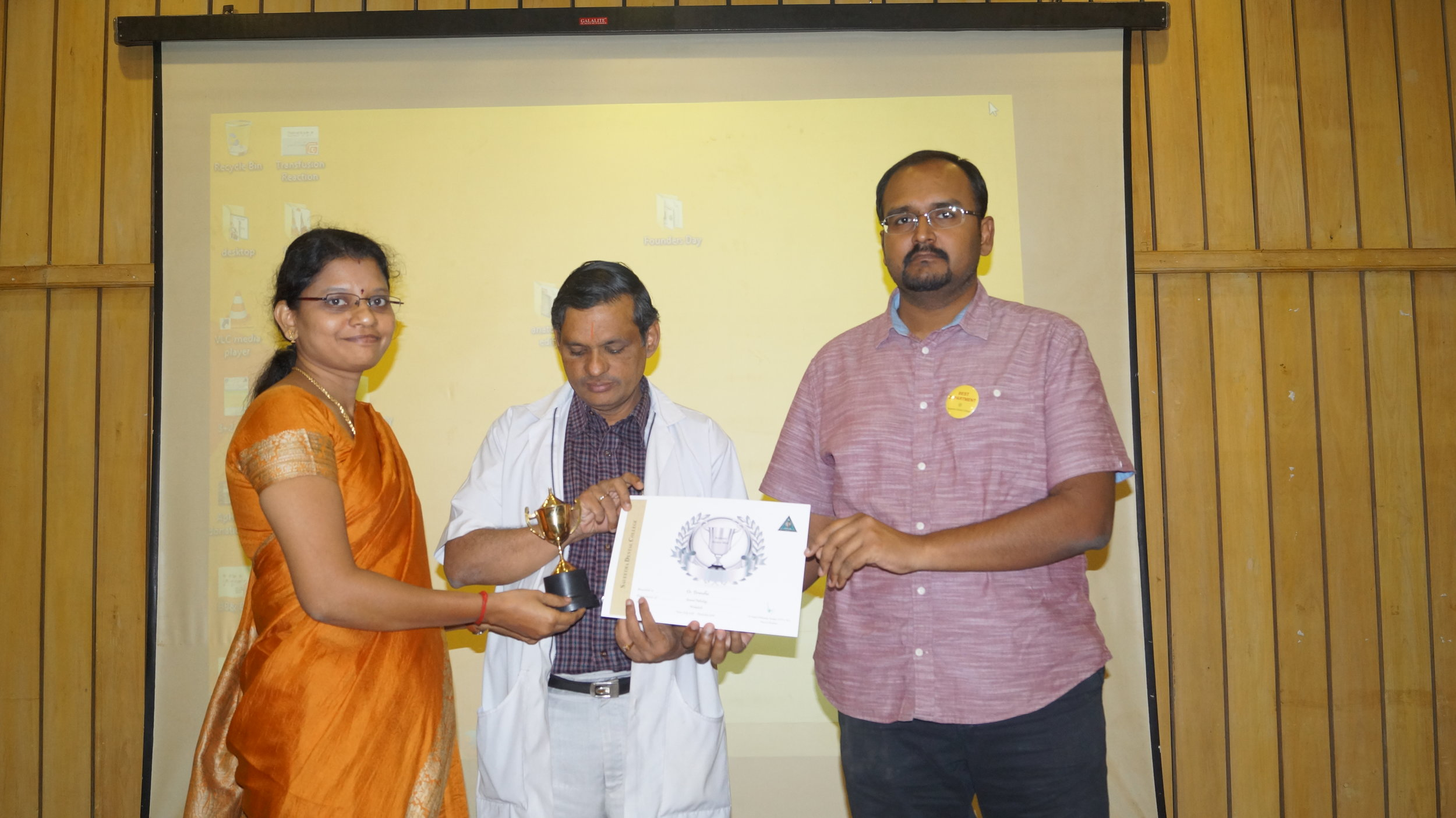 Dr.M.P.Brundha is getting the Workaholic award from the Director of academics and the Dean of Saveetha Dental college.