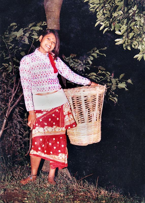 Samjhana Bishankhe in culturele Newari klederdracht en met traditionele draagmand.