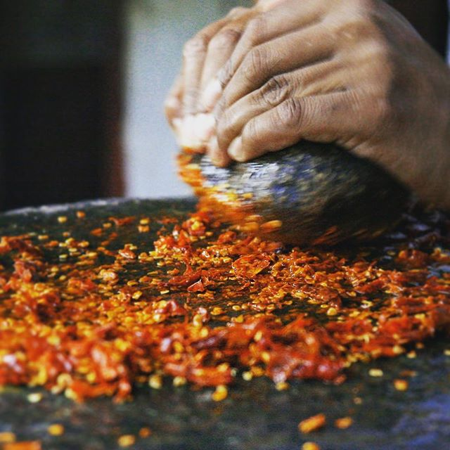 Spices of Nepal. Grinding red chili by hand with a round stone on the surface of a big and heavy flat stone. #chili #spice #flavour #red #chili #veg #vegi #foodie #spicy #traditional #culture #nepal #food #recipe #foodphotography  #flavoursofnepal