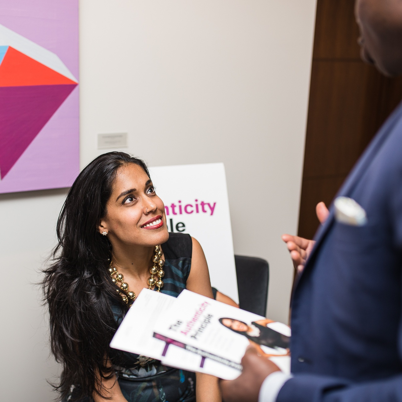 Ritu Bhasin is seated while looking up smiling at a suited man who is getting his booked signed