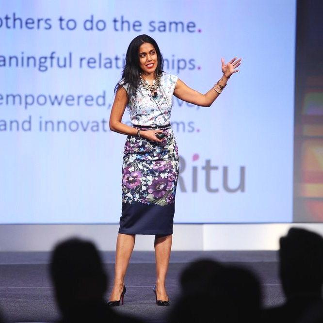 Ritu+Bhasin+wearing+a+fitted+purple+floral+dress%2C+standing+on+a+stage+speaking+in+front+of+a+crowd.jpg