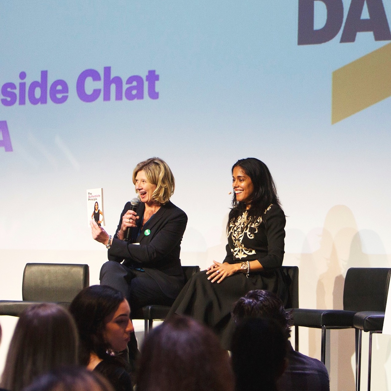 Ritu Bhasin sitting on stage with a blonde woman holding up a copy of Ritu's book The Authenticity Principle.