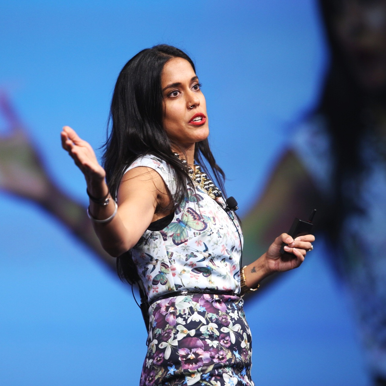Ritu Bhasin wearing a fitted purple floral dress standing on a stage speaking to a crowd