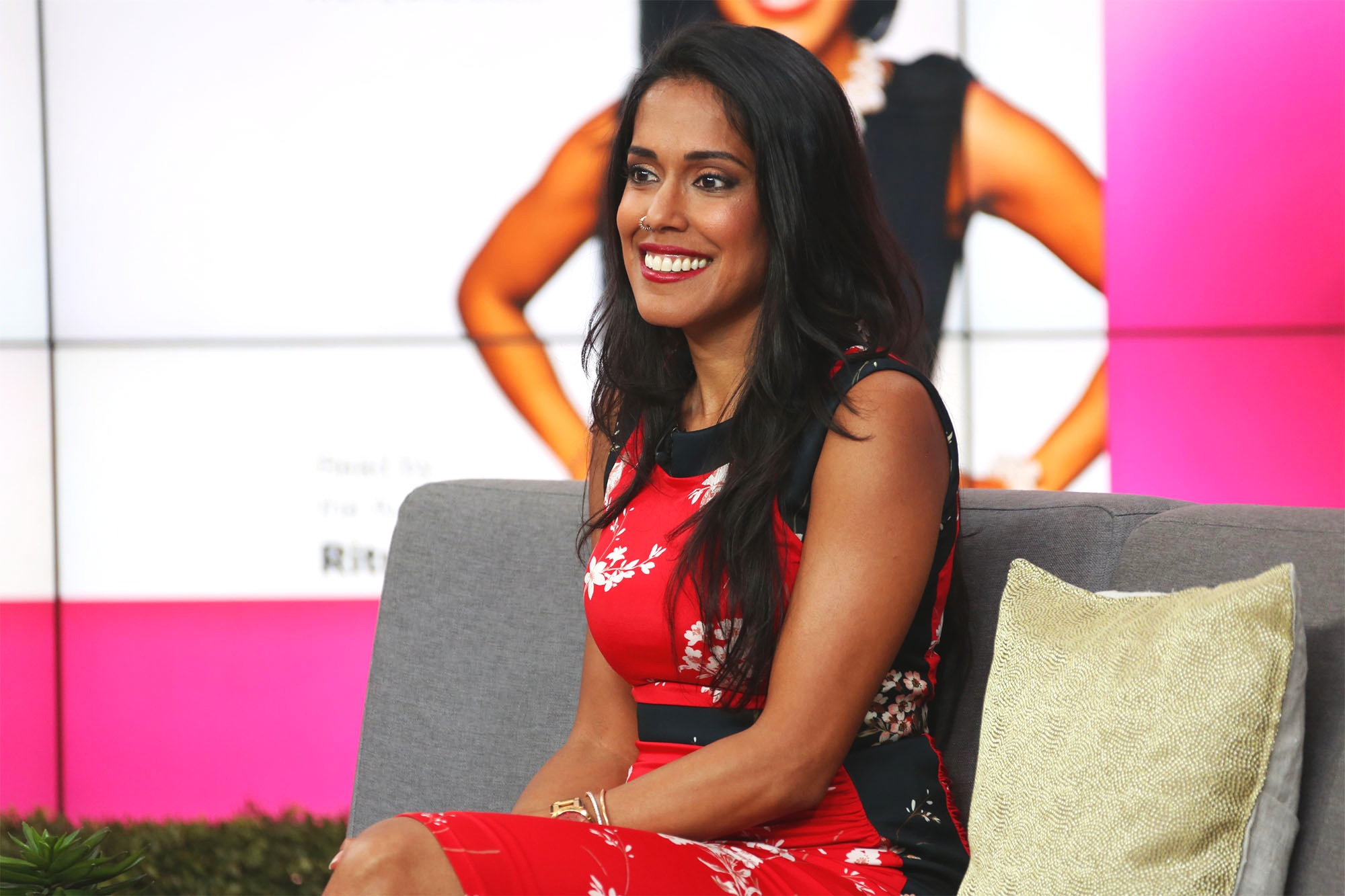 Ritu Bhasin smiling and sitting on a coach on set at CTV's The Social talk show wearing a fitted res dress with black panels on the side.