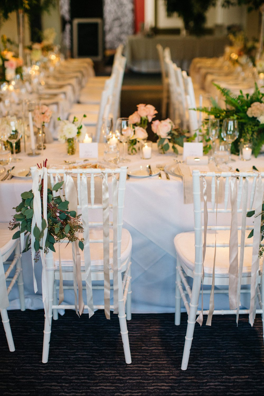 White Tiffany chairs with ribbons for bridal table