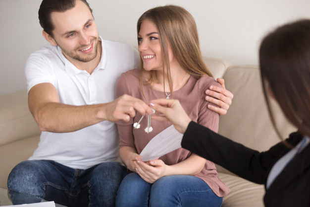 young-smiling-couple-owners-getting-keys-own-house-apartment_1163-4180.jpg