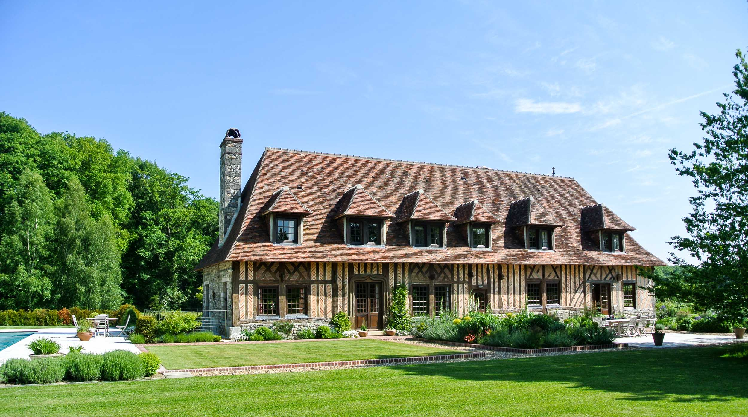 This stunning French farmhouse sits amongst immaculate gardens in Normandy. A sympathetic extension was added by creating a basement and additional tower to the rear of the property,