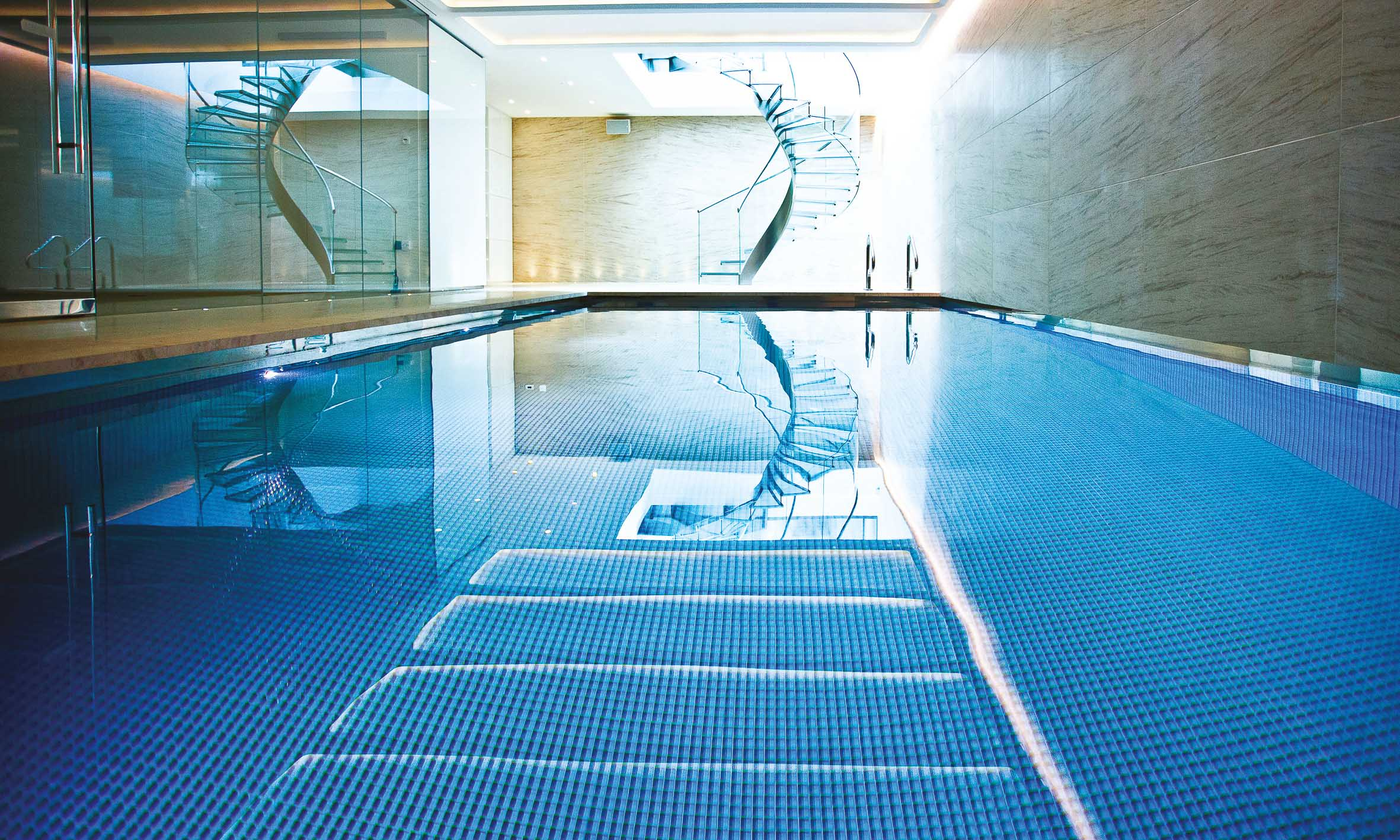 The luxary basement swimming pool. Feature spiral staircase at the end, a sauna and steam room on the left.