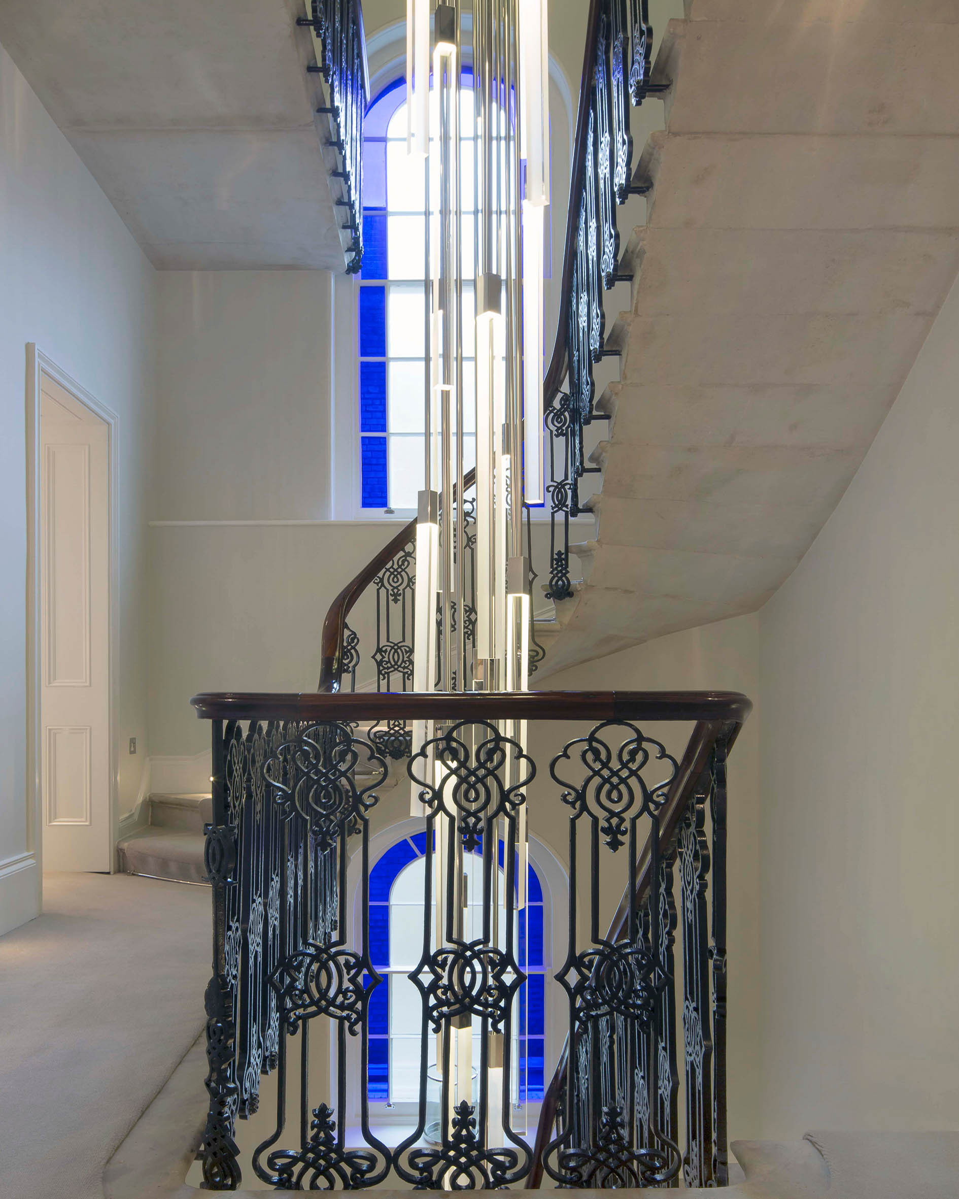 The refurbished main staircase surrounding a new modern light sculpture