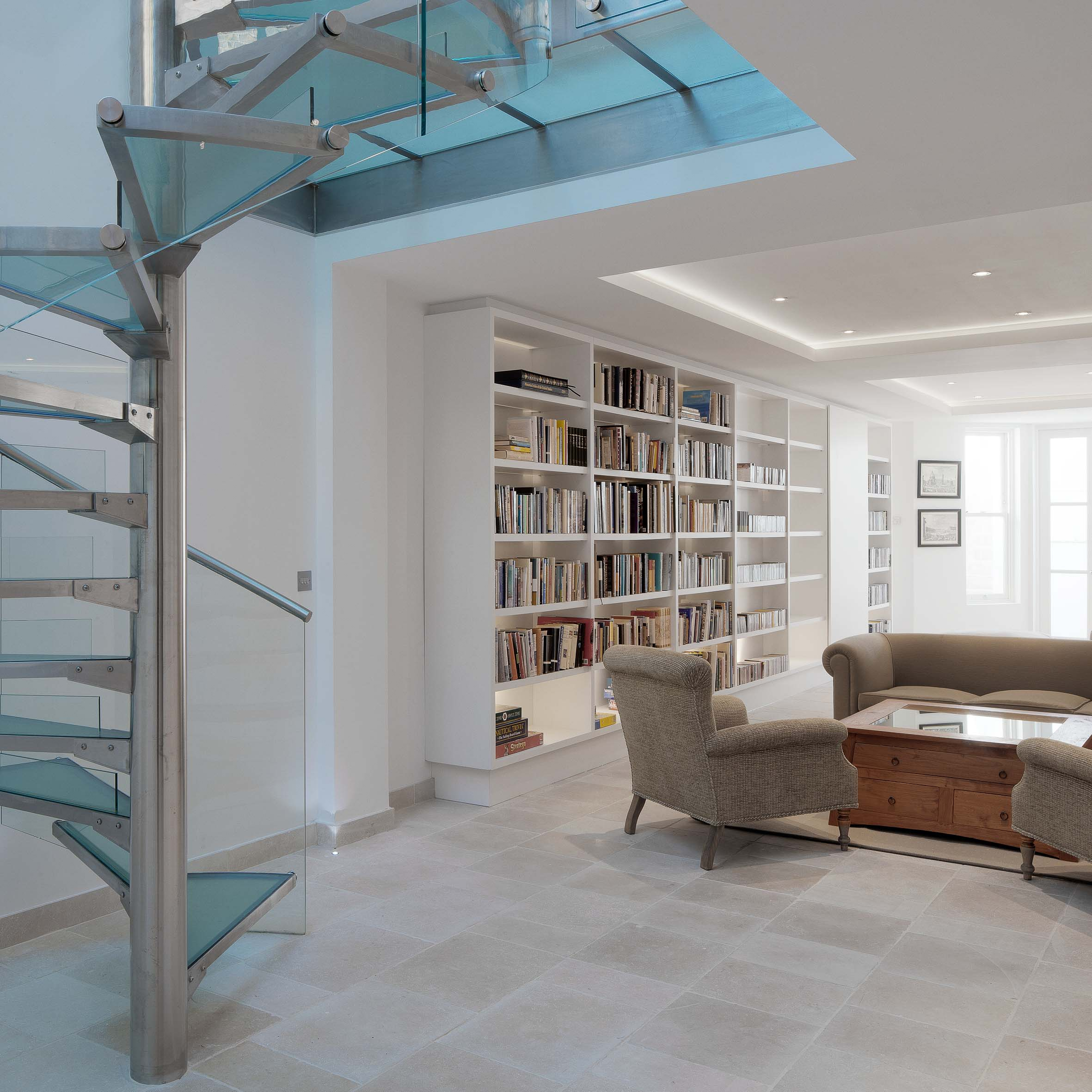 The glass and steel feature staircase and library, living room and coffee table