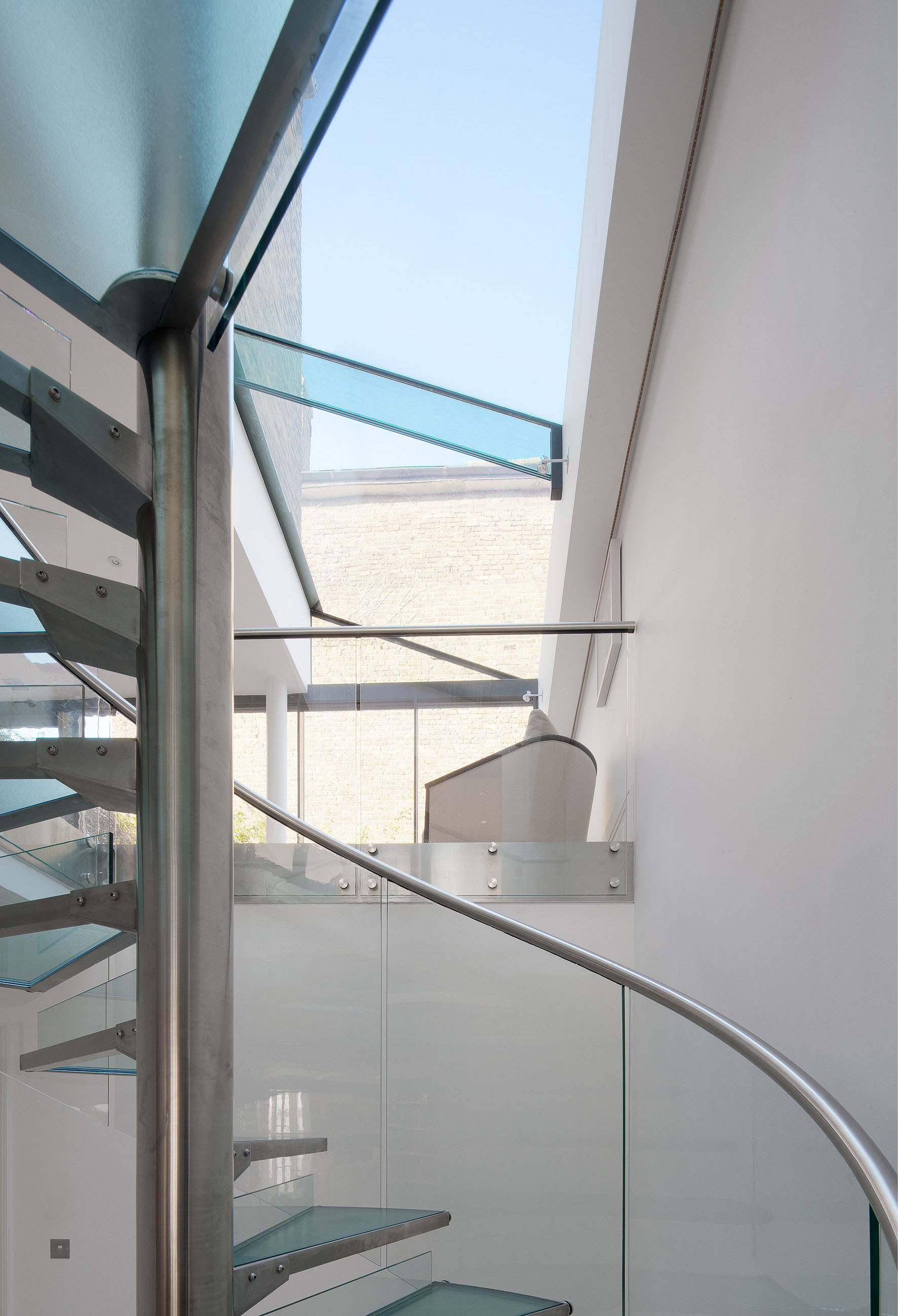 Detail of the glass and steel staircase. View to the living space with modern glass roof extension