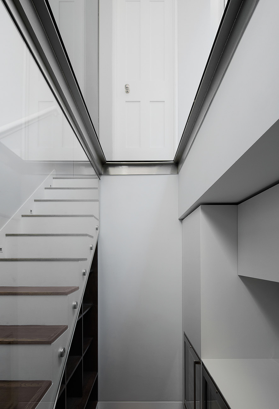 The contemporary glass landing and wooded staircase that link the ground and lower ground floors of the property,.