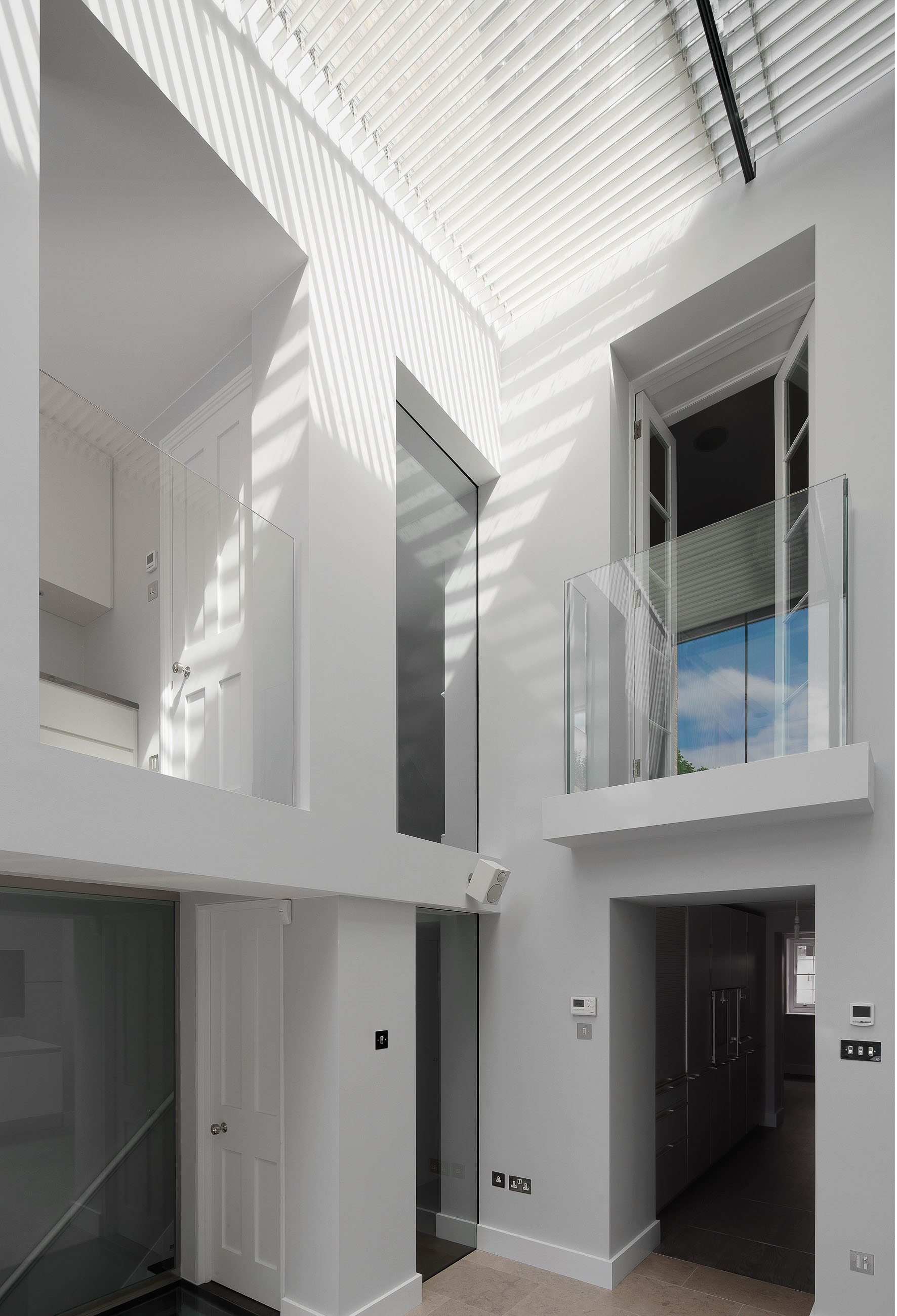 The double height living space with modern glass balustrades. The louversin the ceiling create the most wonderful shadows.