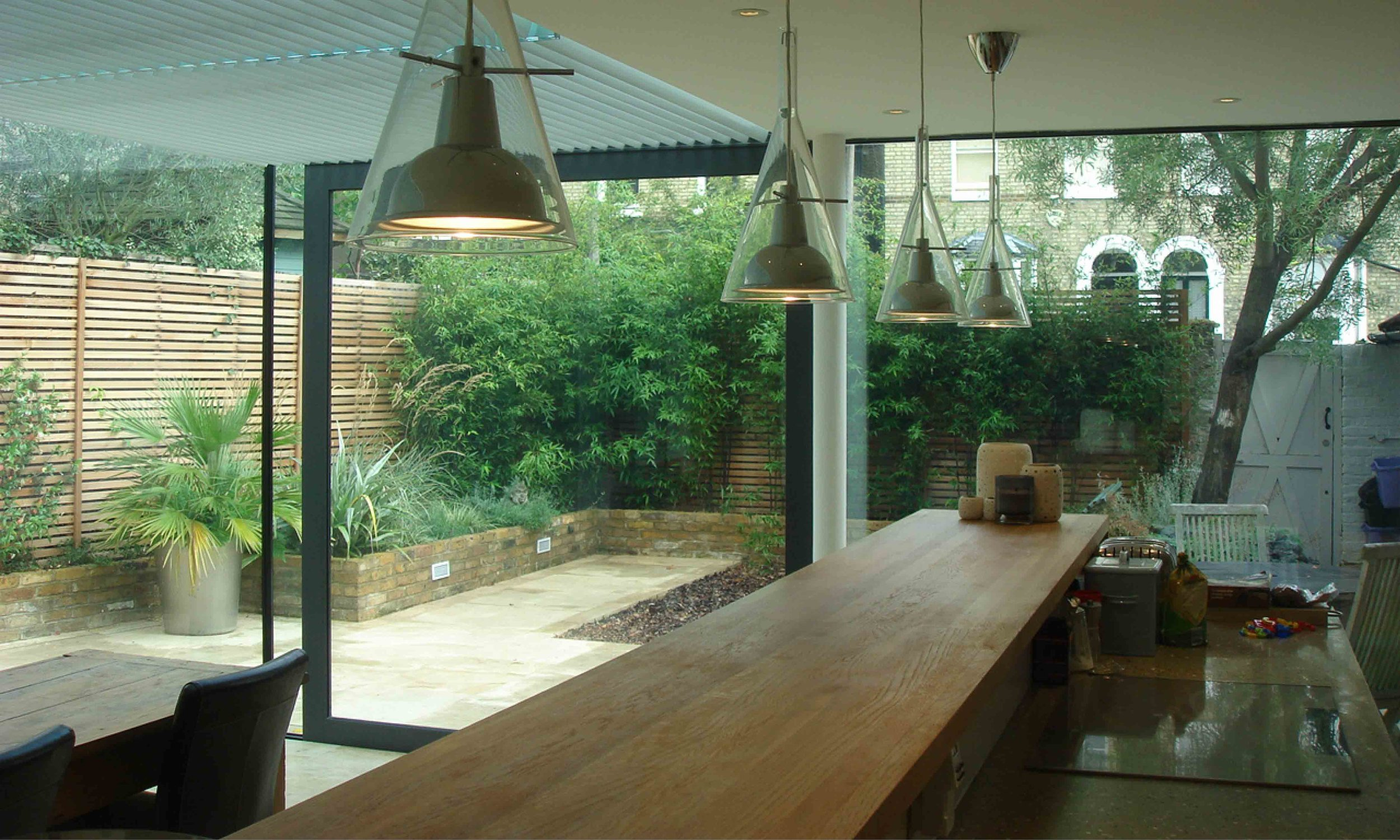 A wooden work surface acts as the focal point tithe kitchen and also balances with the materials used in the garden's landscaping.