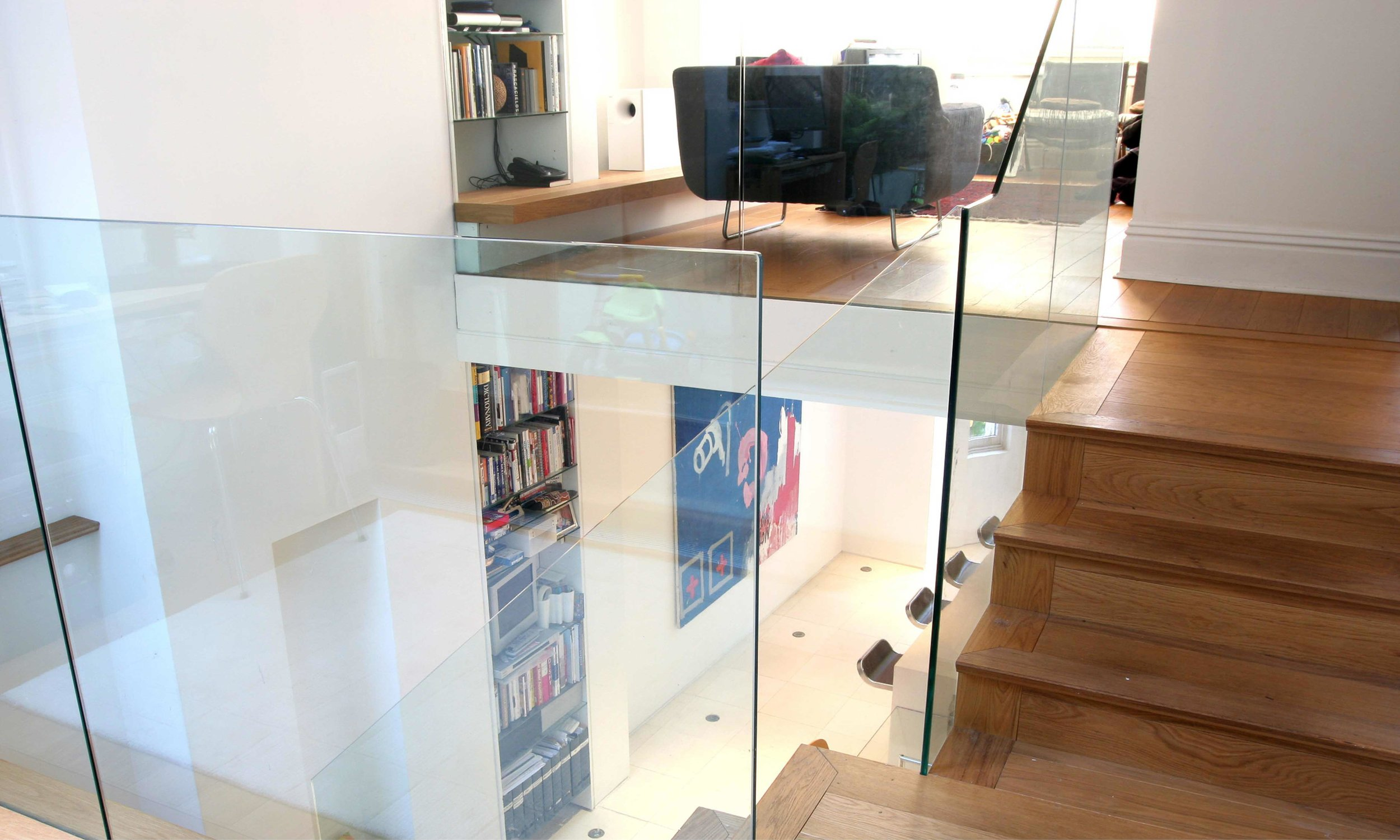 Detail image showing the frames glass balustrades that surround the staircase. These allow natural light to flow down through the living and dining spaces down into the kitchen,